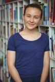 Retrato de la colegiala sonriente que sonríe en biblioteca Fotografía de archivo