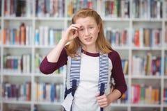 Retrato de la colegiala triste que se coloca con la cartera en biblioteca Fotografía de archivo libre de regalías