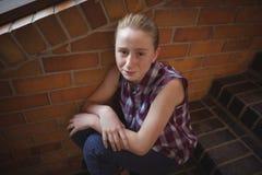 Retrato de la colegiala triste que se sienta solamente en escalera Foto de archivo libre de regalías
