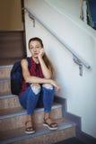Retrato de la colegiala triste que se sienta solamente en escalera Fotografía de archivo libre de regalías