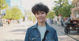 Retrato de la colocación sonriente bonita de la mujer joven al aire libre en día de verano soleado almacen de video