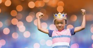 Retrato de la corona que lleva del niño mientras que dobla muscles Imagenes de archivo