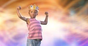 Retrato de la corona que lleva del niño mientras que dobla muscles Foto de archivo libre de regalías
