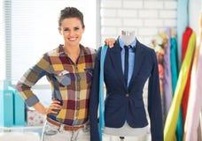 Retrato de la costurera cerca del maniquí en traje Imagen de archivo libre de regalías
