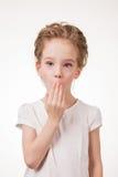 Retrato de la cubierta emocionada sorprendida de la muchacha su boca por la mano Aislado en el fondo blanco Imagen de archivo