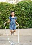 Retrato de la cuerda de salto asiática de la niña en el parque imágenes de archivo libres de regalías