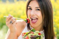 Retrato de la diversión de la muchacha linda que come la ensalada verde al aire libre Foto de archivo libre de regalías