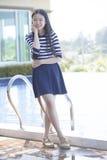 Retrato de la edad adolescente asiática que se coloca al lado de relaxin de la piscina Foto de archivo
