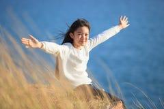 Retrato de la emoción relajante de la muchacha asiática que se sienta en el campo de hierba a Foto de archivo