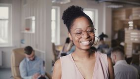 Retrato de la empresaria acertada afroamericana joven hermosa, mirando la cámara en el fondo 4K de la oficina del desván almacen de video