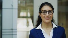 Retrato de la empresaria acertada en vidrios que sonríe en oficina moderna
