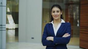 Retrato de la empresaria acertada que sonríe y que mira en cámara en oficina moderna