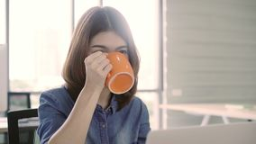 Retrato de la empresaria asiática joven sonriente hermosa que se sienta en la estación de trabajo moderna brillante y que mecanog almacen de metraje de vídeo