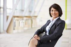 Retrato de la empresaria asiática sonriente, sentándose foto de archivo