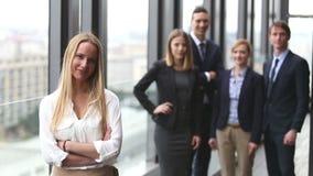 Retrato de la empresaria atractiva que sonríe, colegas en fondo metrajes