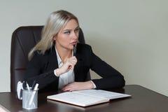 Retrato de la empresaria elegante en el traje que se sienta en la tabla Imagen de archivo libre de regalías
