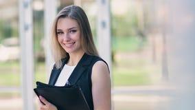 Retrato de la empresaria europea hermosa que sonríe y que saca los vidrios que se colocan al aire libre almacen de video