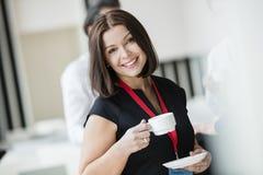 Retrato de la empresaria feliz que sostiene la taza de café en pasillo del seminario foto de archivo