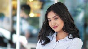 Retrato de la empresaria joven asiática bastante natural que sonríe y que mira la cámara almacen de video
