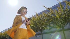 Retrato de la empresaria joven atractiva en gafas de sol que camina en la calle urbana y que usa smartphone moderno afuera almacen de video