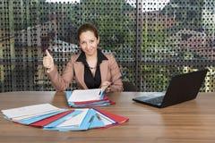 Retrato de la empresaria joven con el pulgar que elabora en el escritorio fotos de archivo
