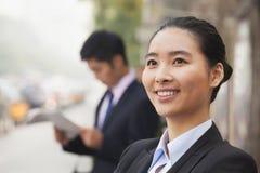 Retrato de la empresaria joven, confiada que parece ausente y que sonríe en la calle, Pekín, China Imágenes de archivo libres de regalías