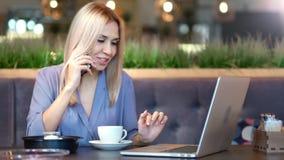 Retrato de la empresaria joven elegante atractiva que sonríe y que habla usando smartphone almacen de video
