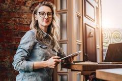 Retrato de la empresaria joven en vidrios de moda, sentándose en café delante del ordenador portátil, sosteniendo la tableta, tra fotos de archivo