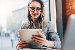 Retrato de la empresaria joven en vidrios de moda, sentándose en café delante del ordenador portátil, usando la tableta, trabajan fotografía de archivo libre de regalías