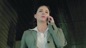 Retrato de la empresaria joven que habla en el teléfono almacen de metraje de vídeo