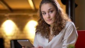 Retrato de la empresaria joven que sostiene la tableta y que mira inquiringly en cámara en fondo de la oficina foto de archivo