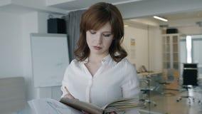 Retrato de la empresaria joven que toma notas en suplente del cuaderno en la oficina con la ciudad grande almacen de metraje de vídeo