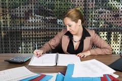 Retrato de la empresaria joven que trabaja en el escritorio imagenes de archivo