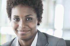 Retrato de la empresaria joven sonriente con el pelo corto que mira la cámara, el principal y los hombros foto de archivo libre de regalías