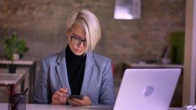 Retrato de la empresaria de pelo corto de mediana edad en el funcionamiento de vidrios con el smartphone, sonrisas a la cámara en metrajes