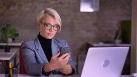 Retrato de la empresaria de pelo corto rubia de mediana edad en los vidrios que hacen la selfie-foto usando el teléfono móvil en  almacen de metraje de vídeo