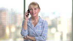 Retrato de la empresaria que habla en el teléfono en oficina almacen de metraje de vídeo