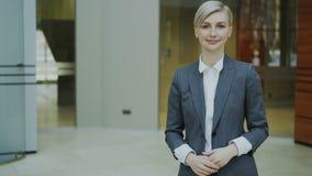 Retrato de la empresaria rubia acertada que sonríe y que mira en cámara en oficina moderna