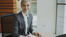 Retrato de la empresaria rubia atractiva que se sienta en la escritura de la tabla en el cuaderno que sonríe en cámara en oficina