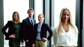 Retrato de la empresaria rubia atractiva que sonríe, colegas en fondo metrajes