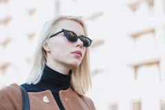 Retrato de la empresaria rubia joven en ciudad del otoño La muchacha tiene mirada elegante, gafas de sol y perforación de la nari imagenes de archivo
