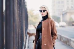 Retrato de la empresaria rubia joven en ciudad del otoño La muchacha tiene mirada elegante, gafas de sol y perforación de la nari fotos de archivo
