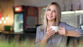 Retrato de la empresaria sonriente atractiva que goza del café de consumición de la rotura que sostiene la taza blanca grande almacen de metraje de vídeo