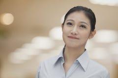 Retrato de la empresaria sonriente joven en una camisa del botón abajo, dentro, foco en primero plano Fotos de archivo