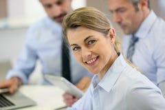 Retrato de la empresaria sonriente que assiste a la reunión del trabajo Foto de archivo libre de regalías