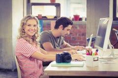 Retrato de la empresaria sonriente que trabaja con el colega en oficina Imagenes de archivo