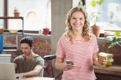 Retrato de la empresaria sonriente que usa smartphone mientras que sostiene el café en officce Imagenes de archivo