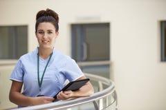 Retrato de la enfermera de sexo femenino With Digital Tablet en hospital Imagenes de archivo