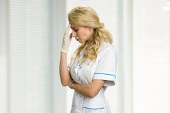 Retrato de la enfermera de los jóvenes con dolor de cabeza Fotografía de archivo
