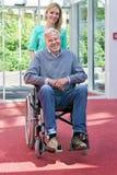 Retrato de la enfermera Pushing Senior Man en silla de ruedas Foto de archivo libre de regalías